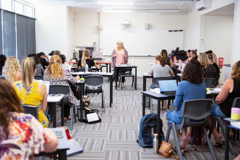 teacher aide students in a classroom leanring teaching strategies
