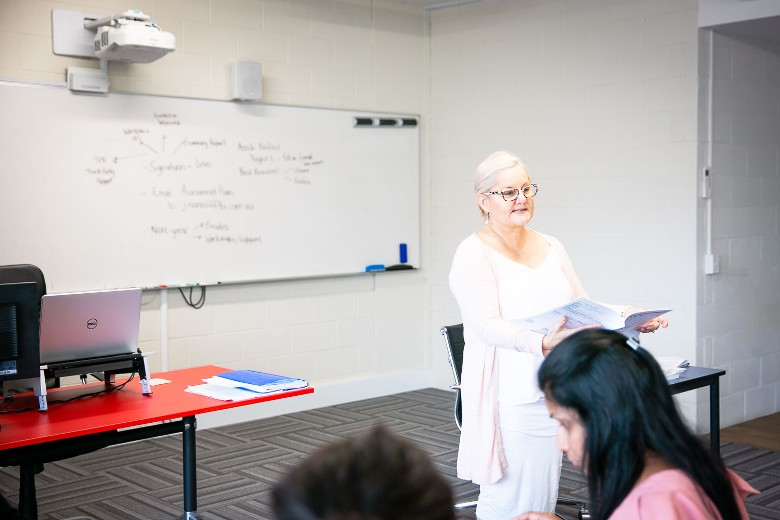 Female teacher in class teaching group of adult students