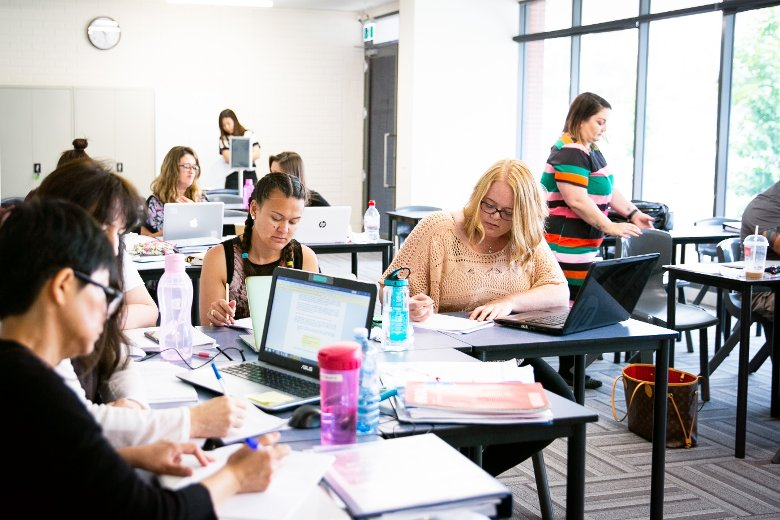 Image of ITAC students in classroom reading and studying to become a teacher aide