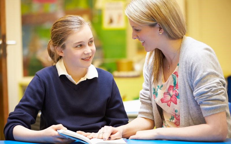 Teacher within a classroom engaging a student with a discussion.