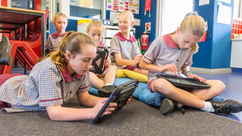 Group of 5 school aged children in a classroom using tablets.