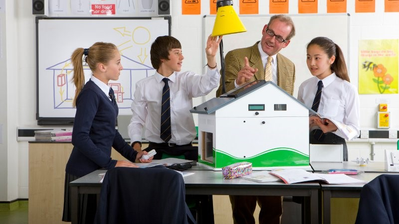 Group of high school students and teacher building a model sized house.