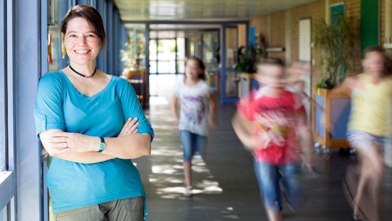 Teacher assistant supervising in a school hallway.