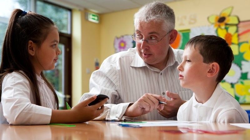 Teacher assistant pictured assisting a small group of students.