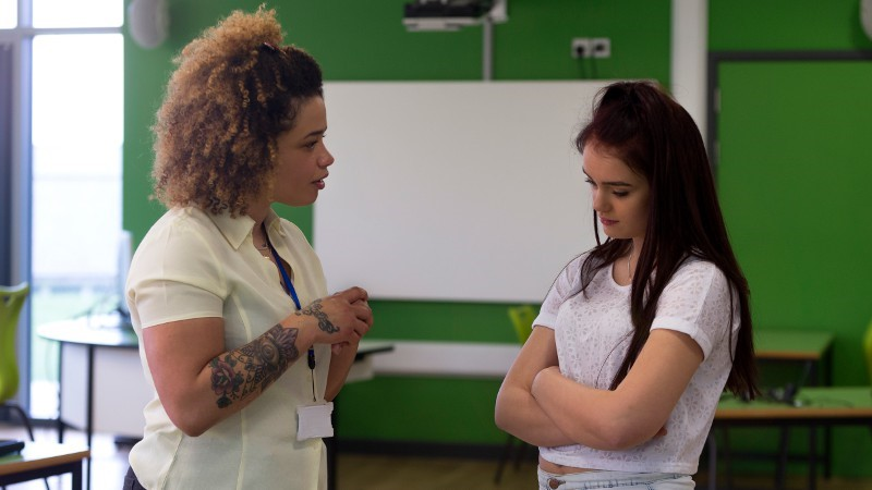 Teacher talking to a student in a classroom environment.