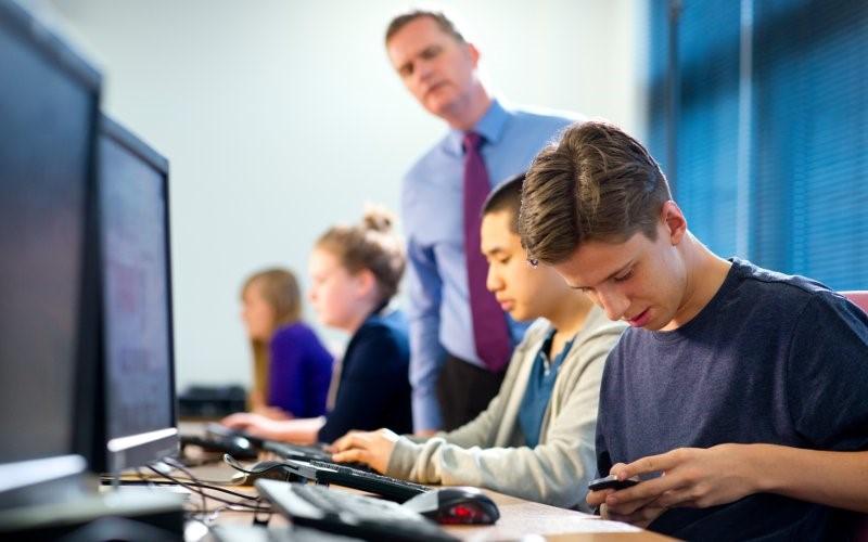 Observant teacher aide in a classroom.