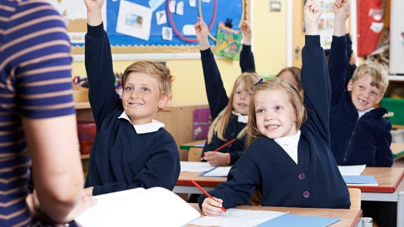Children in a classroom raising their arms to answer a question.