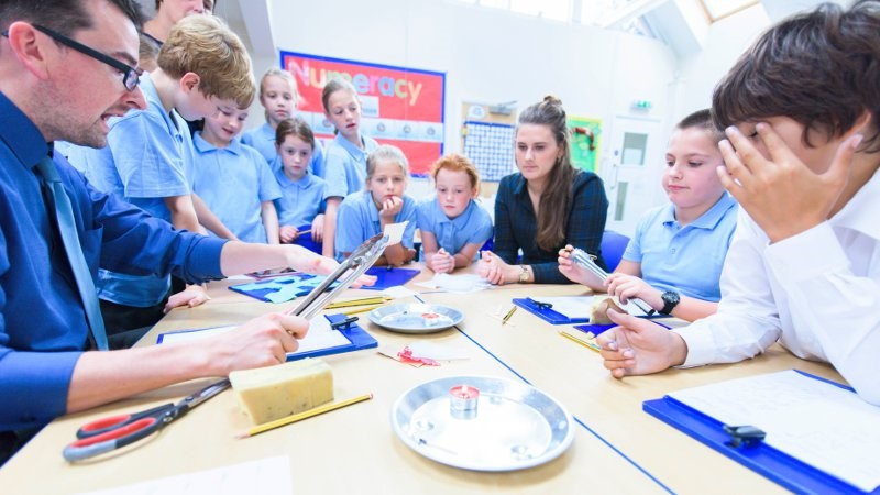 teacher aide working with students in a school