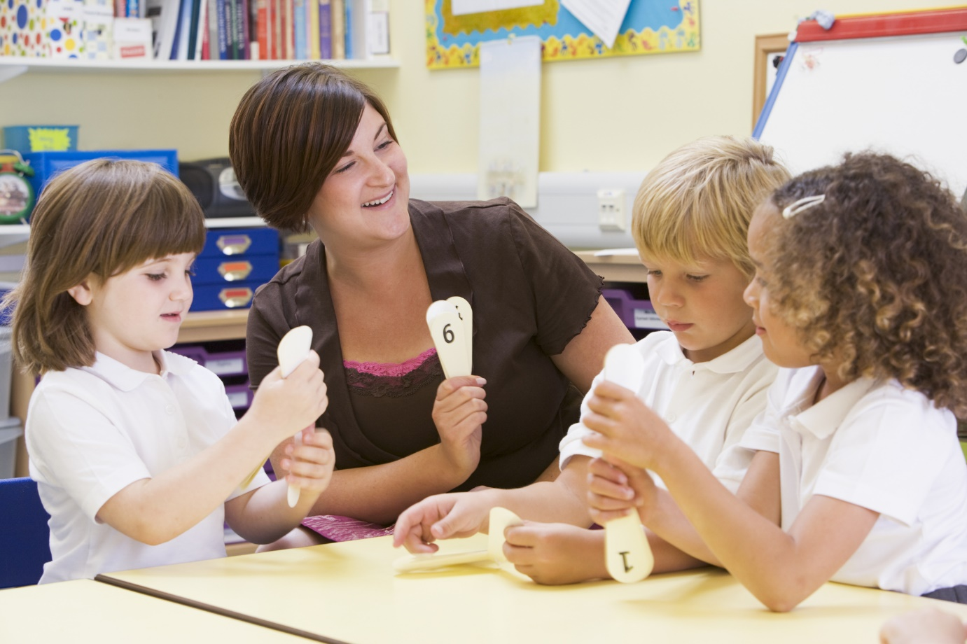 Female teacher aide with young students playing a game.