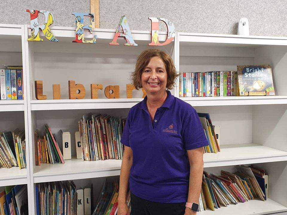 Teacher aide on placement in front of books and bookshelf.