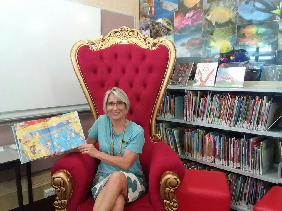Teacher aide sitting in big chair in reading corner.