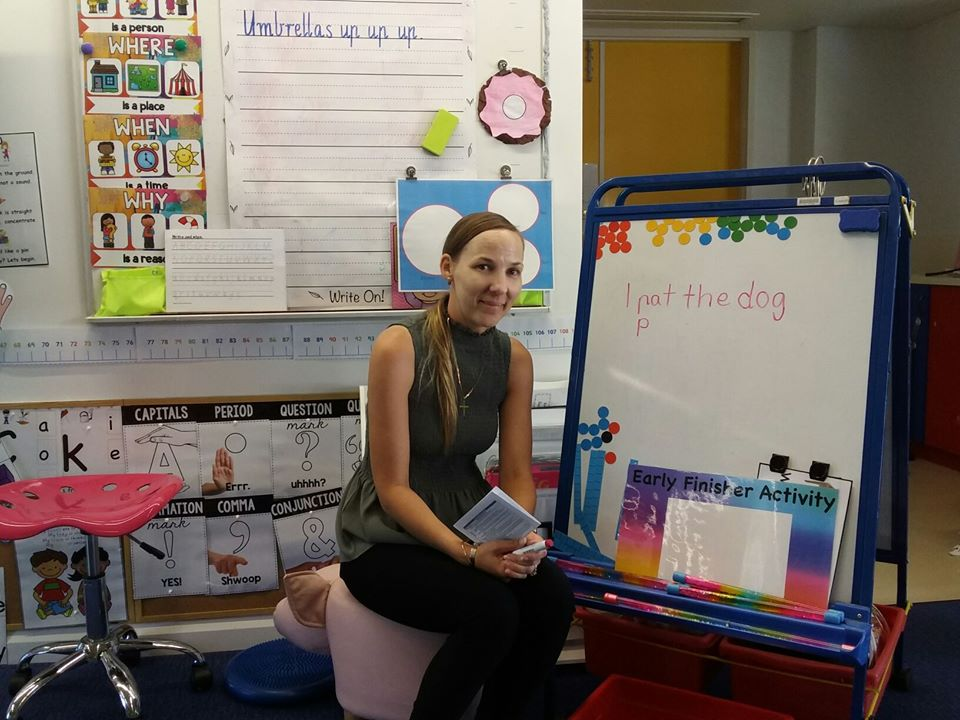 Teacher aide in the CHC30213 Certificate III in Education Support with whiteboard and marker in reading lesson.