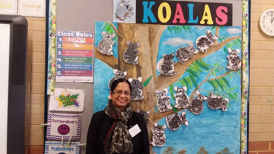 Smiling teacher assistant standing in front of class art board.