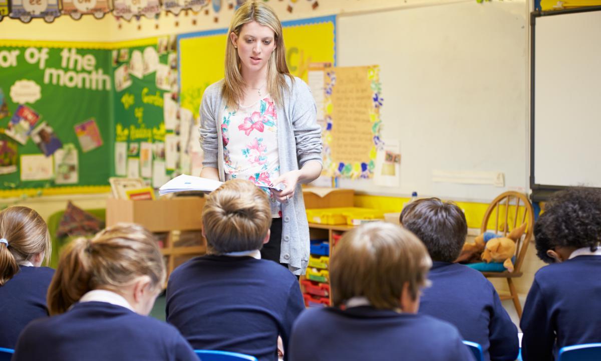 female teacher aide speaking towards classroom