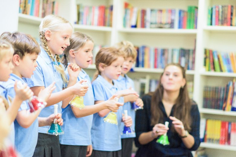 Youg teacher aide with students who are singing