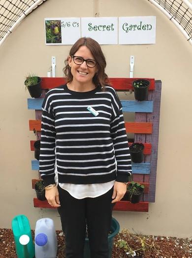 Female in black and white jumper standing in secret garden in school