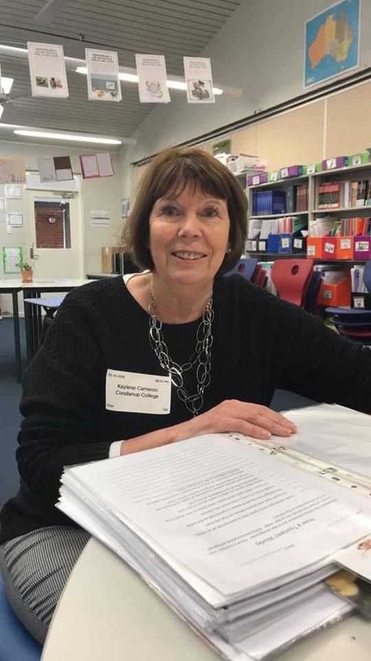 teacher aide with resource folder of student activities in classroom