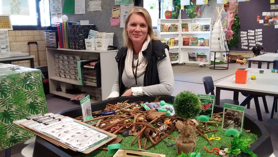 teacher aide at desk in front of resources for teaching kids about animals and plants.