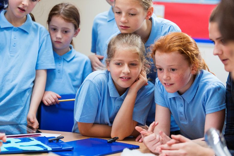 Group of young girls in blue uniform and a learning support officer in class eagerly engaged in an activity