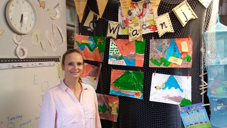 Learning Support Officer Stands in front of colourful work samples made by students.