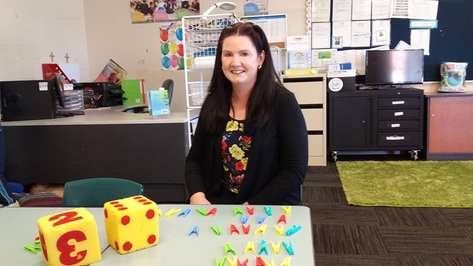 Female LSO sits at desk with equipment for learning including pegs and toys.