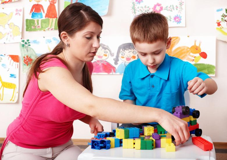 teacher aide in red shirt helps child with blocks and toys