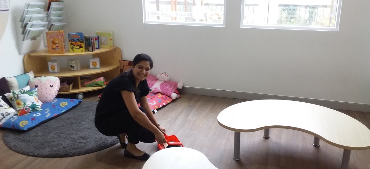 Female teacher aide with dust pan and shovel doing light cleaning in classroom.