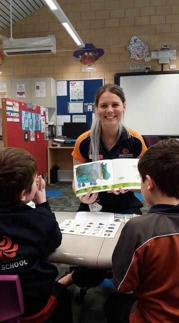 school support officers reading to children while on placement