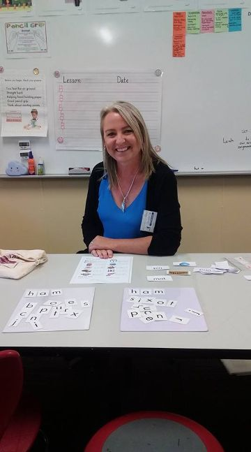 ITAC student in a placement sitting in front of phonics reading cards