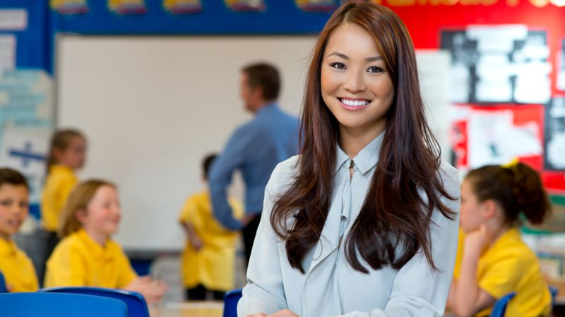 Image of a teacher assistant working in a active classroom..