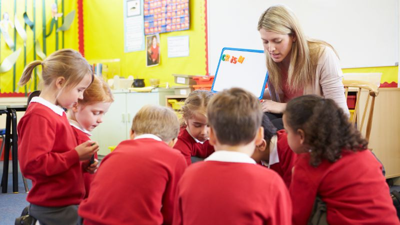 Teacher assistant supporting a group of 6 young students in a classroom.