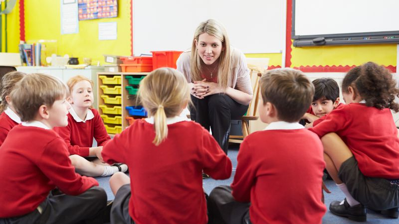 Teacher assistant is pictured confidently assisting students in a class setting.
