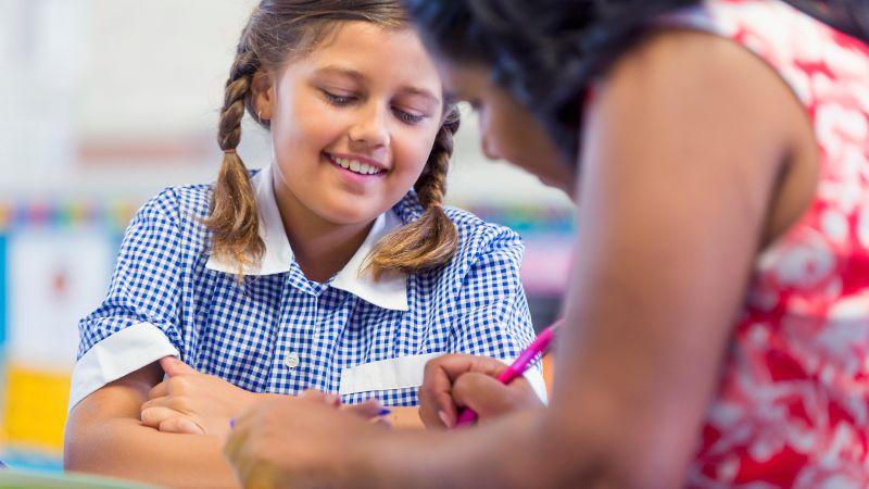 Teacher aide utilising best practice skills in a classroom setting.