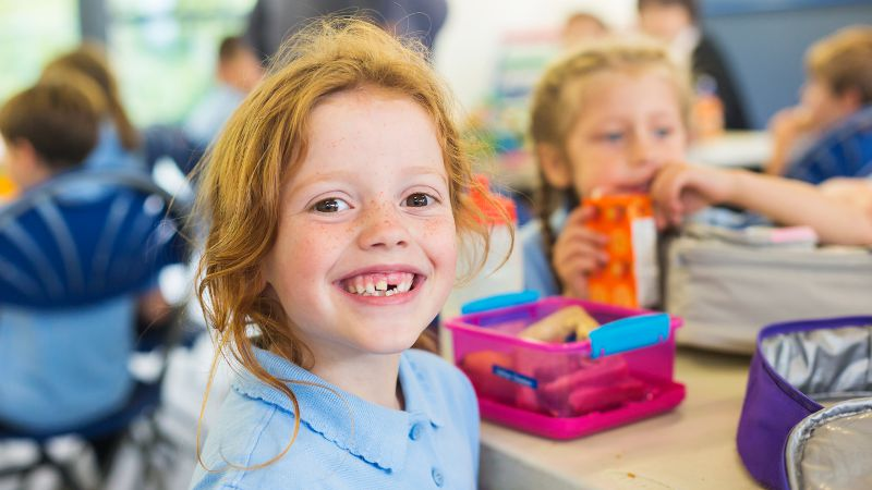 Smiling student shown in a very active classroom.