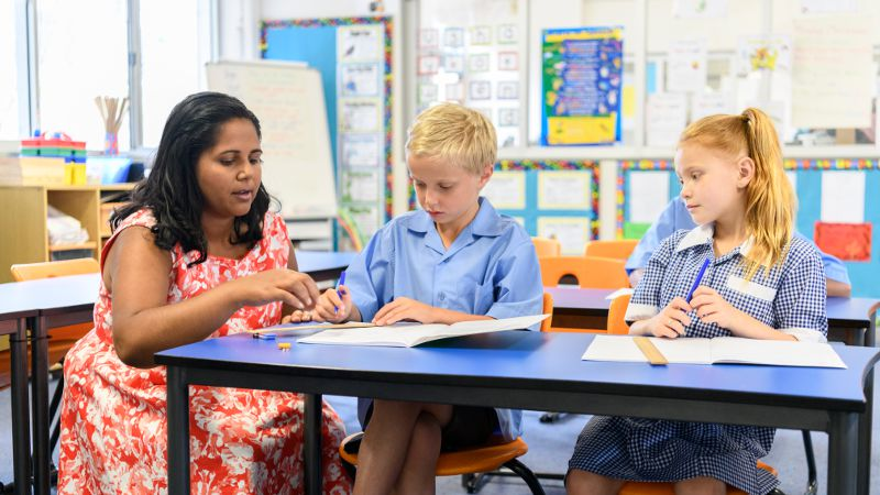 A teacher aide sitting at a table in a classroom with two young students
