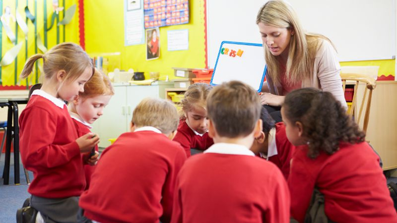 Teacher assistant working with a group of 7 students in a school setting.