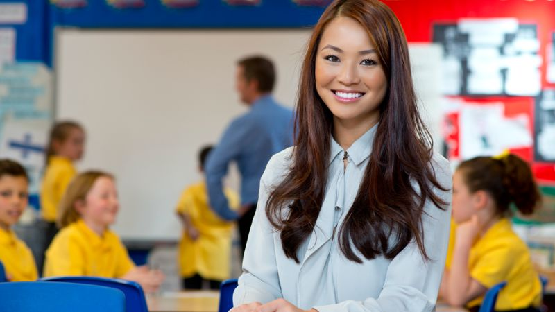 A smiling teacher aide shown in a classroom with learning activities going on in the background.