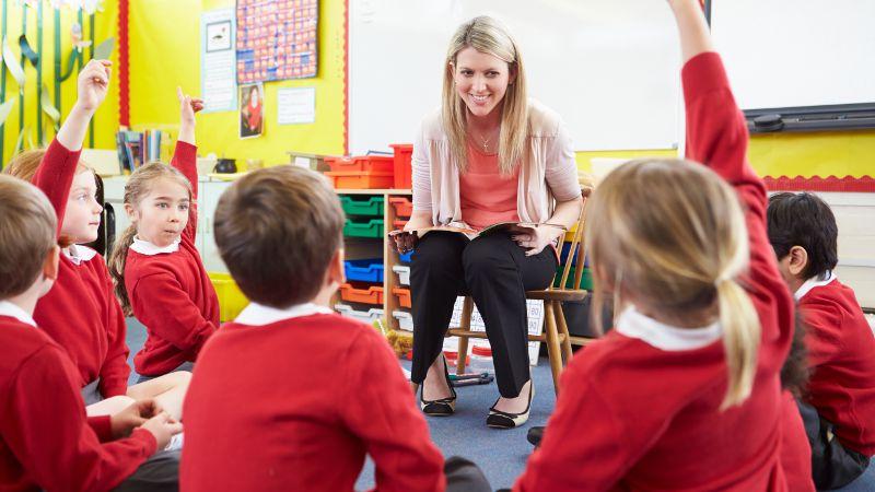 Teacher aide shown during a class presentation.