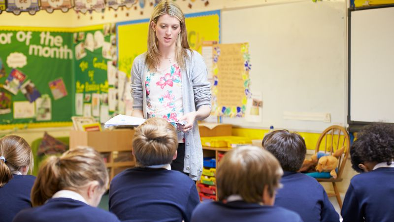 Teacher assistant standing while reading a book to a classroom full of students.