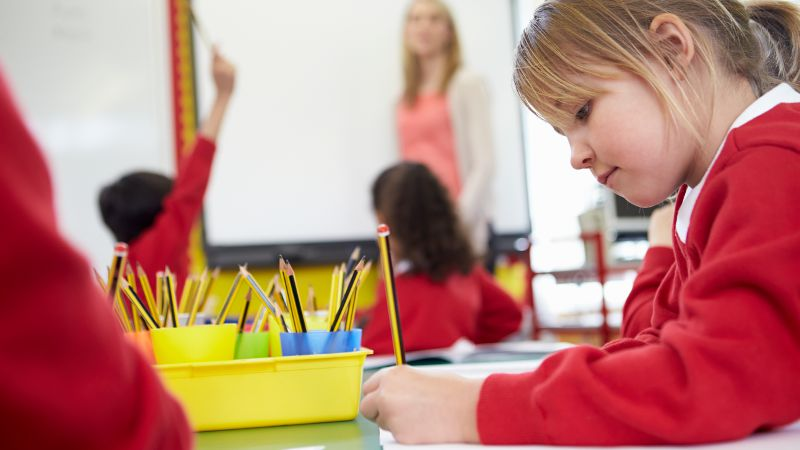 Student in a classroom writing on paper with a pencil while a teacher is discussing a topic in the background.