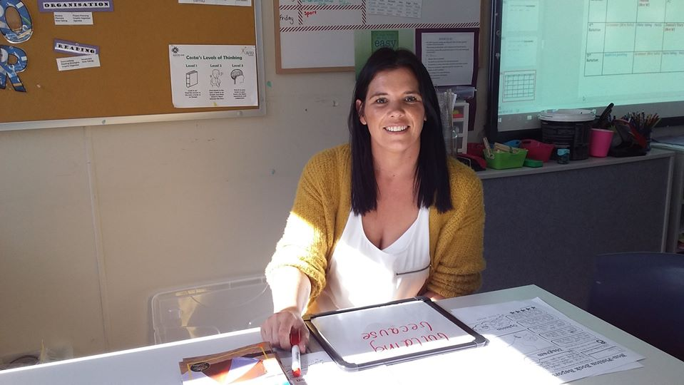 Teacher aide sitting at desk in a classroom setting.