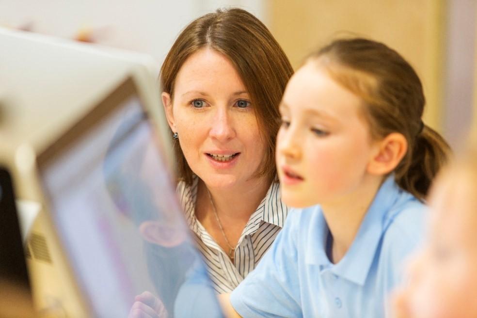Teacher aide working in a computer lab.