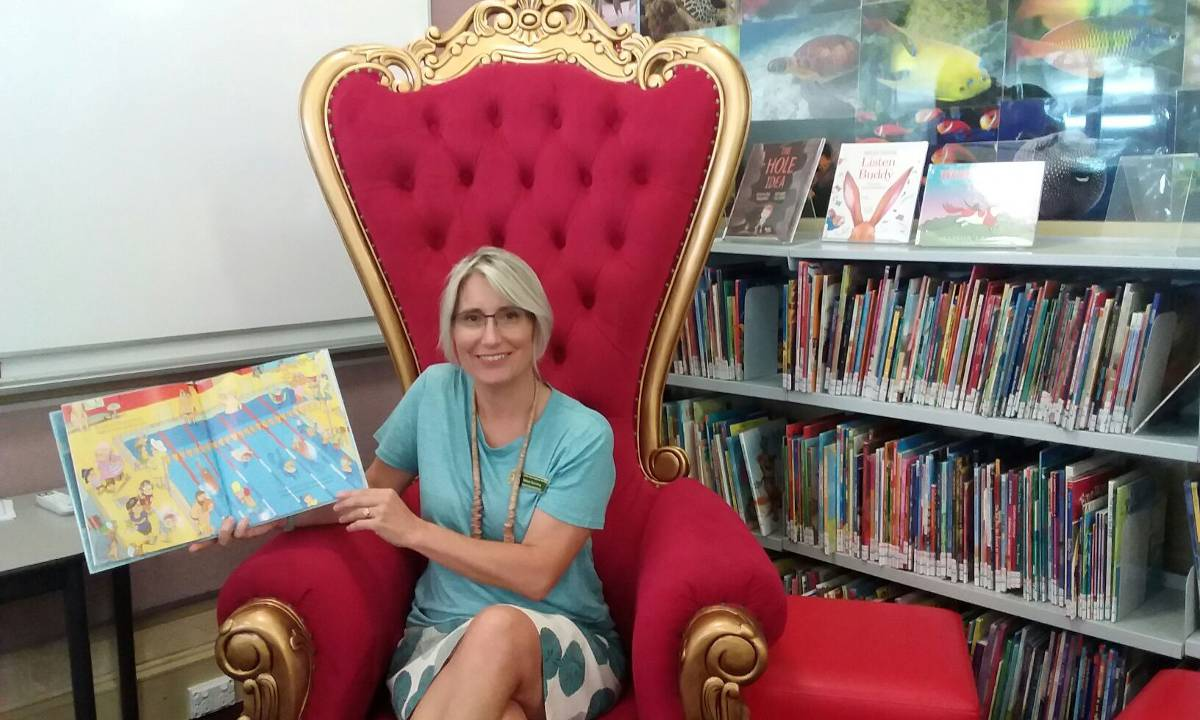 A teacher assistant sitting in the reading corner of a classroom..