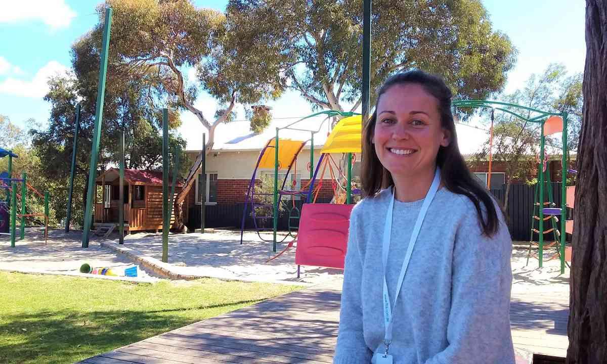 Teacher aide in a school playground environment.