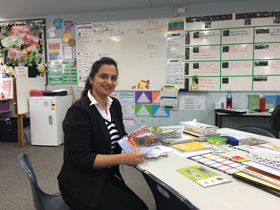 Teacher assistant in colourful classroom with pencil and worksheets.