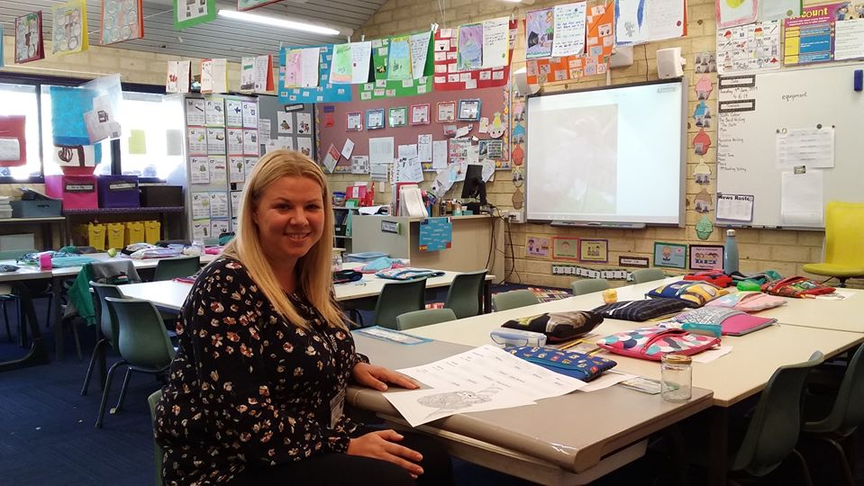 Female adult student sitting at desk in decorated lower year classroom.