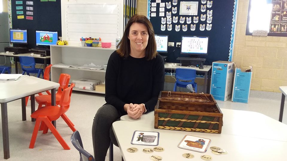 Teacher aide wearing jumper sitting at children's desk with fun play-based reading activity.