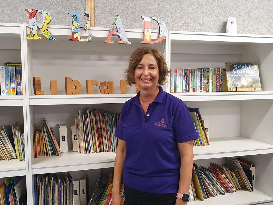 Teacher aide in school uniform standing in front of bookshelf.