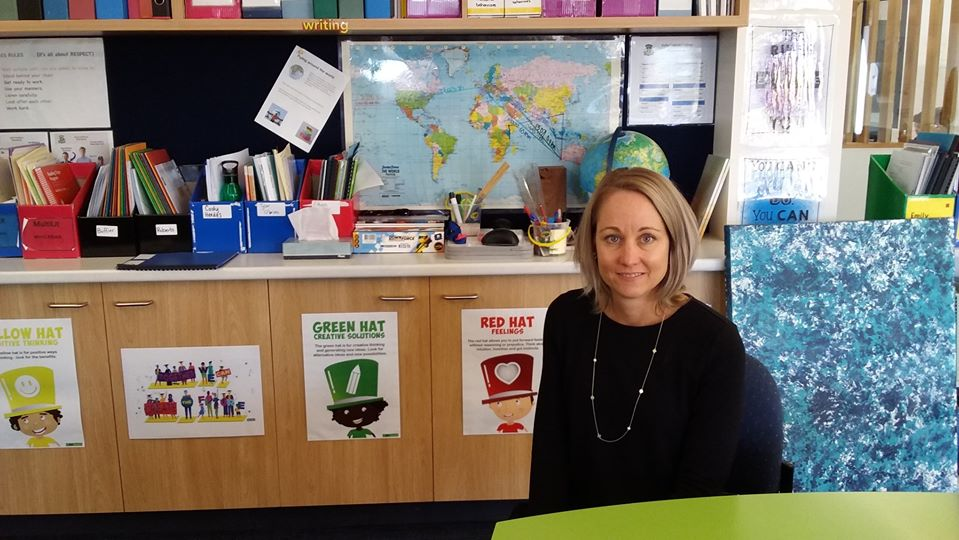 teacher aide student in front of school resources such as books and map of world.