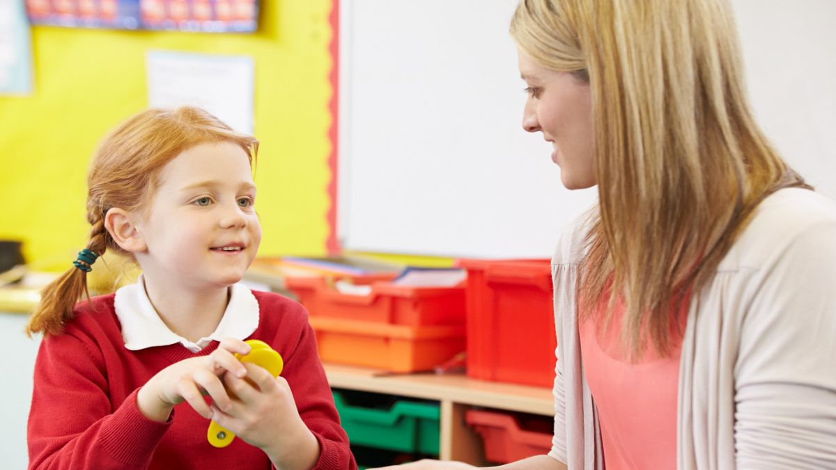 Teacher assistant working with a student in a classroom.